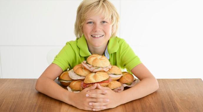 Portrait of boy with arms around pile of sandwiches